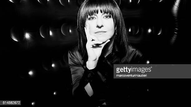 Woman, black satin shirt, black background