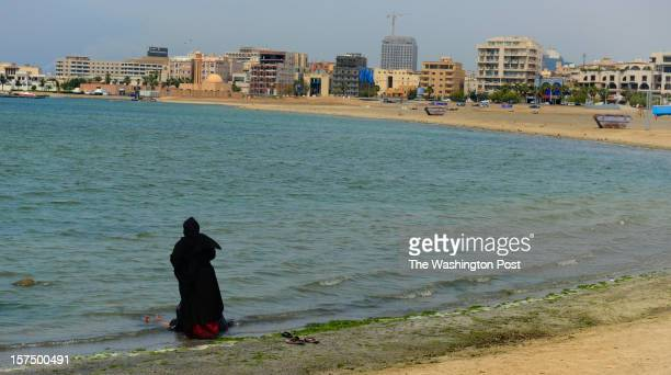 A woman blocks the view of her friend bathing in her abaya on the beach Jeddah Saudi Arabia on September 25 2012 In spite of the wealthy images...