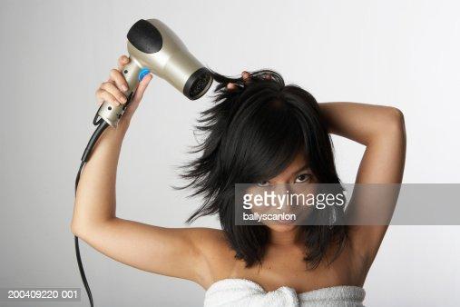 Woman blow drying hair in bath towel : Stock Photo