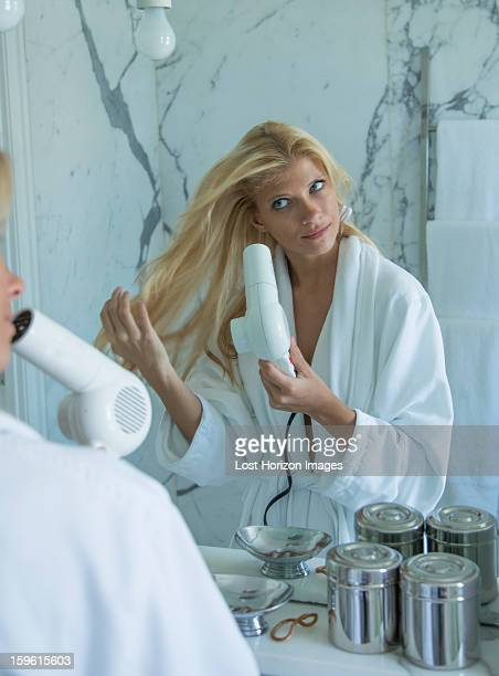 Woman blow drying her hair in bathroom