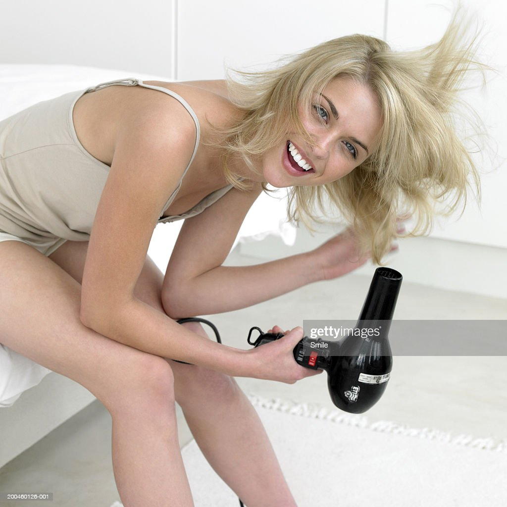 Woman blow drying her hair smiling, portrait : Stock Photo