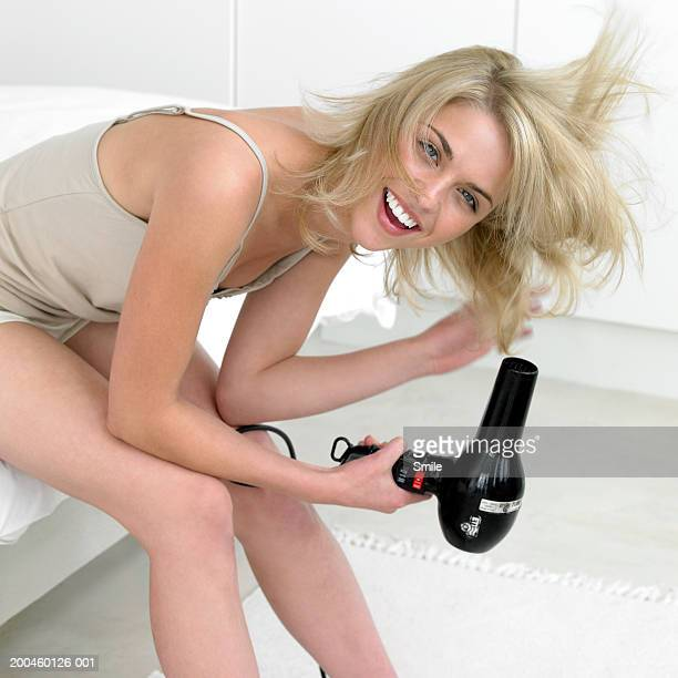 Woman blow drying her hair smiling, portrait