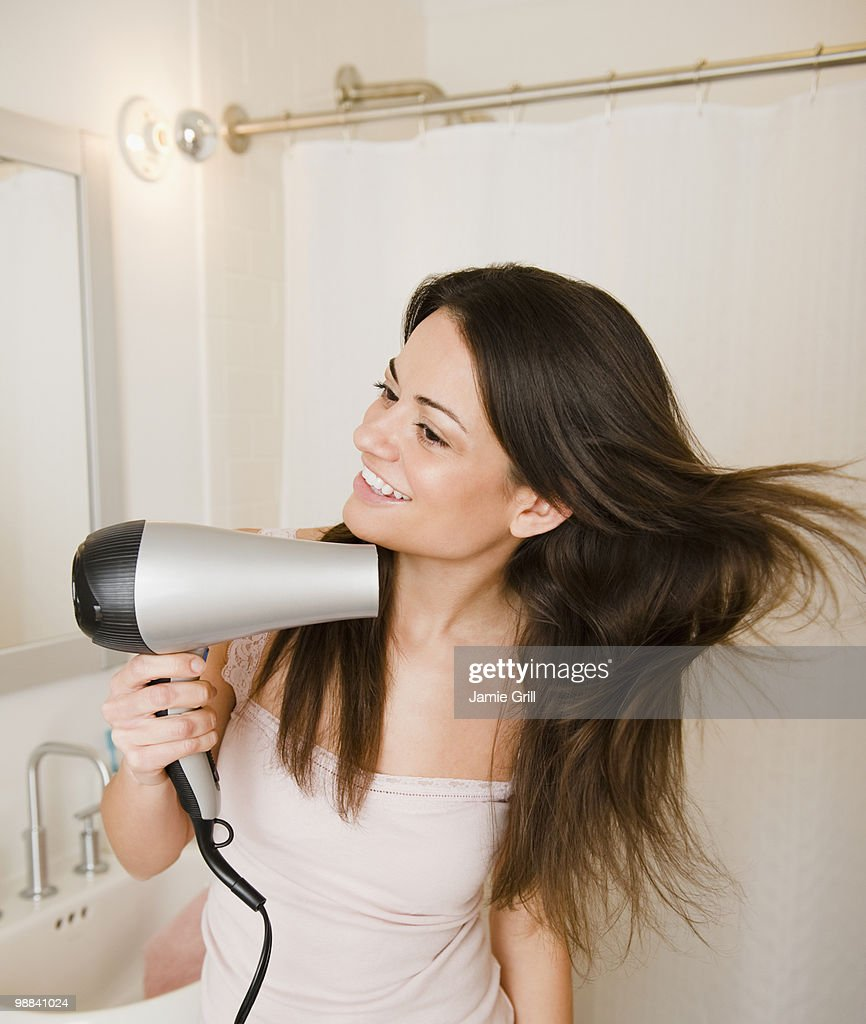 Woman blowdrying hair in bathroom