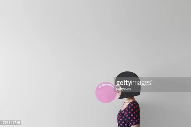 Woman blowing a conceptual bubble gum bubble