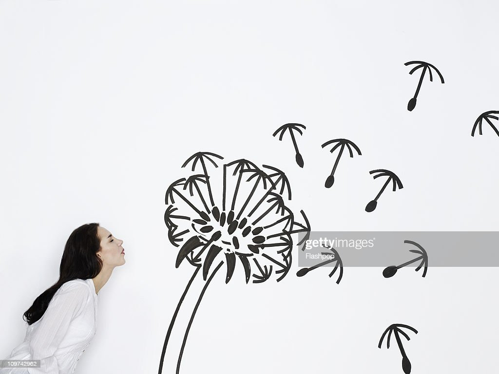 Woman blowing a dandelion clock : Stock Photo