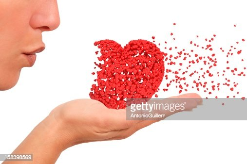 Woman blowing a heart : Stock Photo