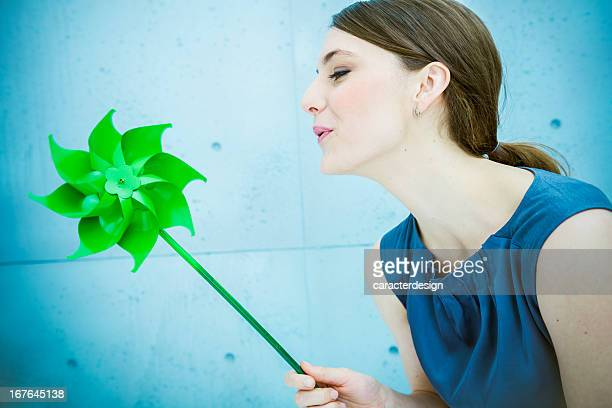 Woman blowing a pinwheel in nature