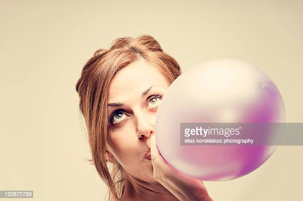 Woman blowing balloon
