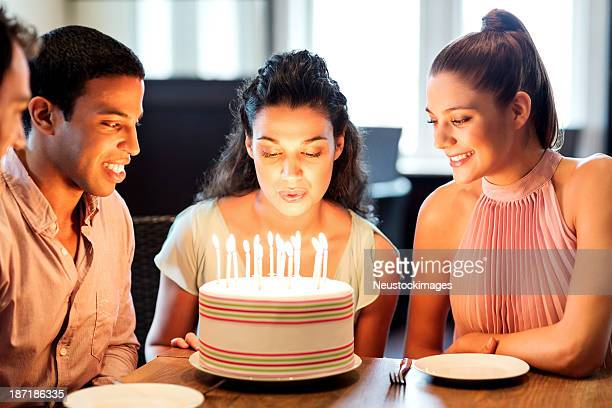 Woman Blowing Birthday Candles On Cake