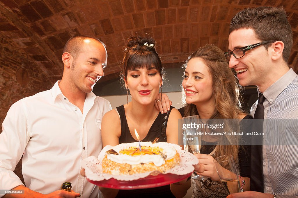 Woman blowing candle on birthday cake : Stock Photo