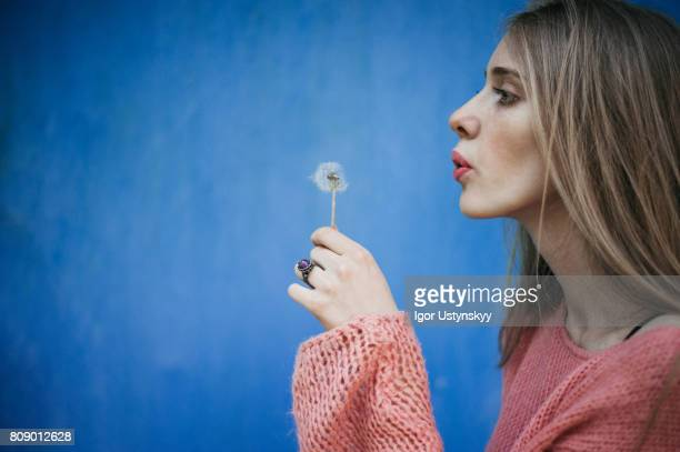 Woman blowing dandelion on the background of blue wall