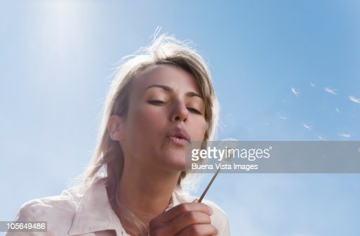 Woman blowing dandelion  : Stock Photo