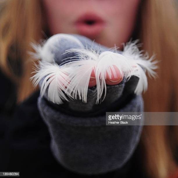 Woman blowing feathers