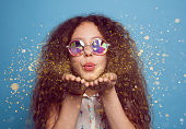 Young curly girl in crystal sunglasses blowing on hands with golden glitters on blue background.