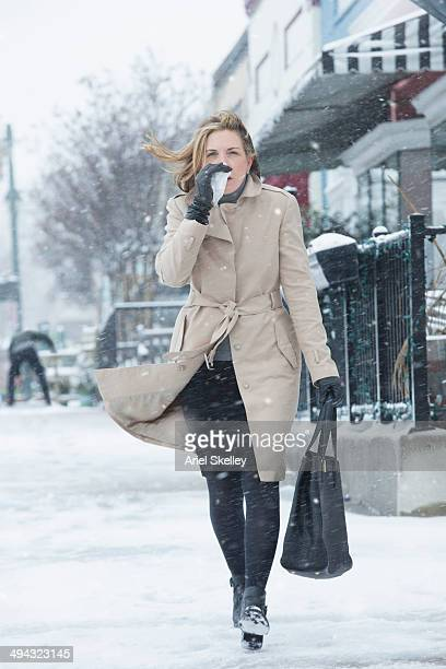 Woman blowing her nose and walking in snow