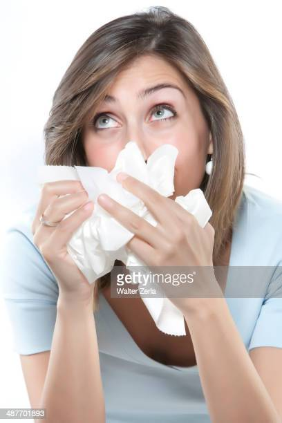 Woman blowing her nose into tissues