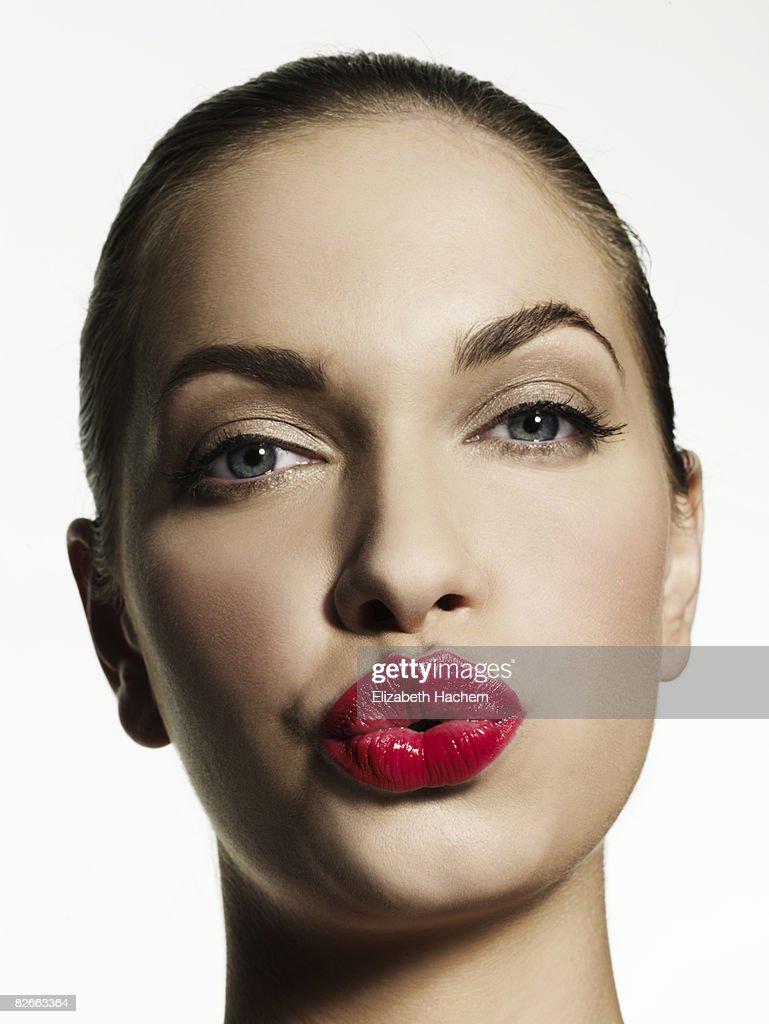 Woman blowing kiss towards camera : Stock Photo