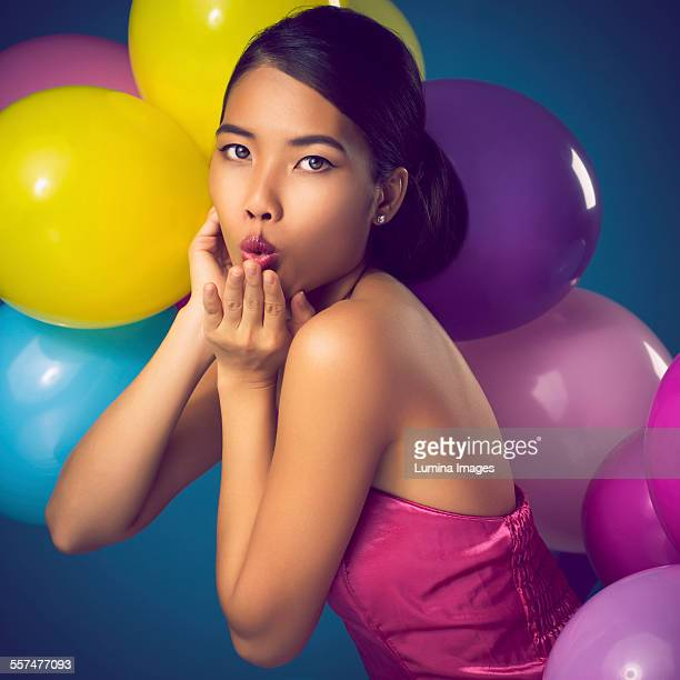Woman blowing kiss with party balloons