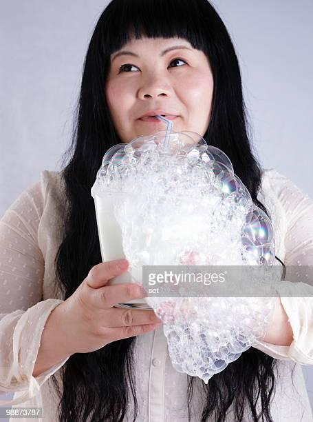 woman blowing milk bubbles