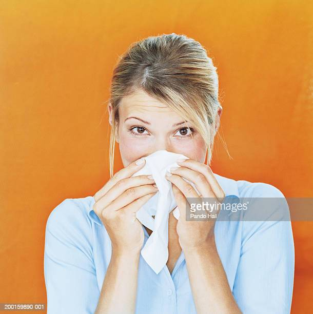 Woman blowing nose on tissue, portrait, close-up