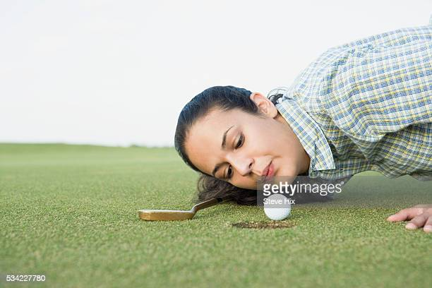 Woman blowing on a golf ball