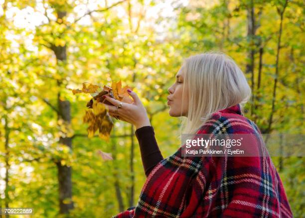 Woman Blowing On Dried Leaves In Forest