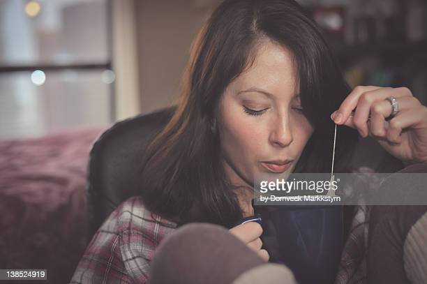Woman blowing on hot cup of tea