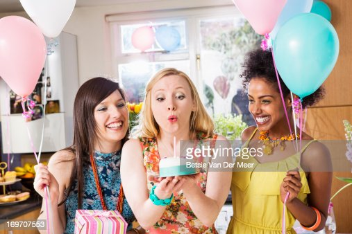 Woman blowing out candle on birthdaycake. : Stock Photo
