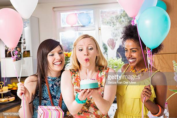Woman blowing out candle on birthdaycake.