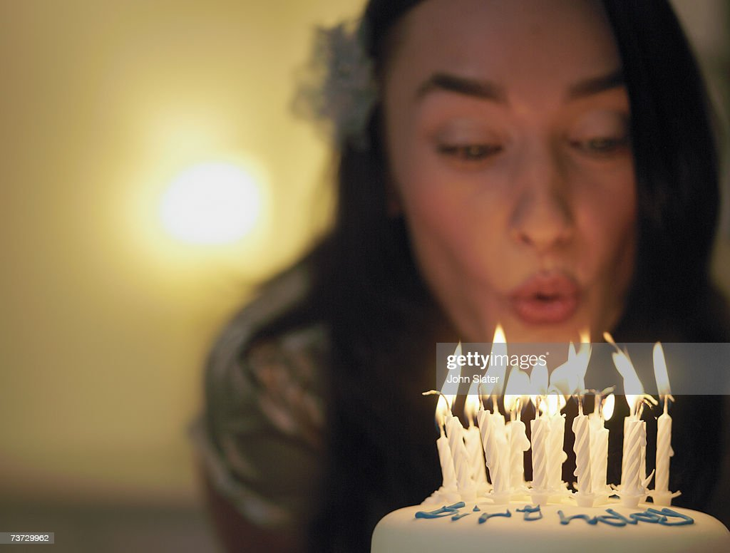 'Woman blowing out candles on birthday cake, focus on candles'