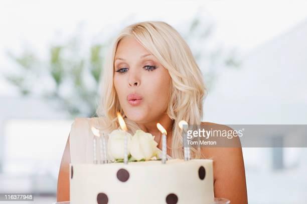 Femme soufflant les bougies sur le gâteau d'anniversaire