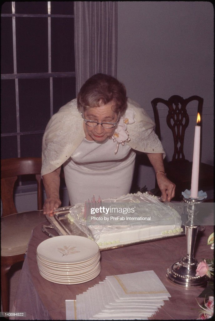 Woman blowing out her birthday candles : Stock Photo