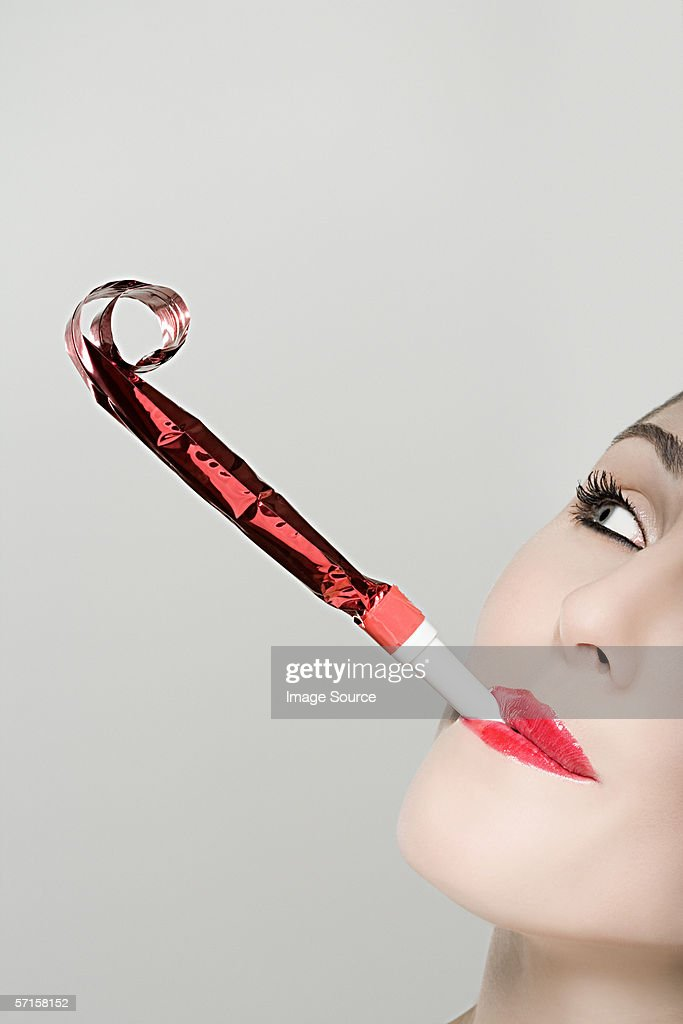Woman blowing party horn blower : Stock Photo