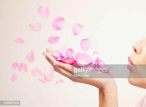Woman 吹くピンクのバラの花びら
