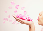 Woman blowing pink rose petals