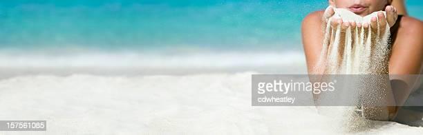 Femme souffle sur ses mains de sable