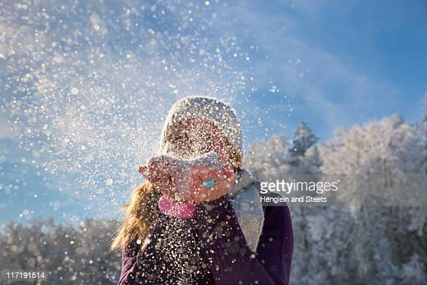 Woman blowing snow at viewer