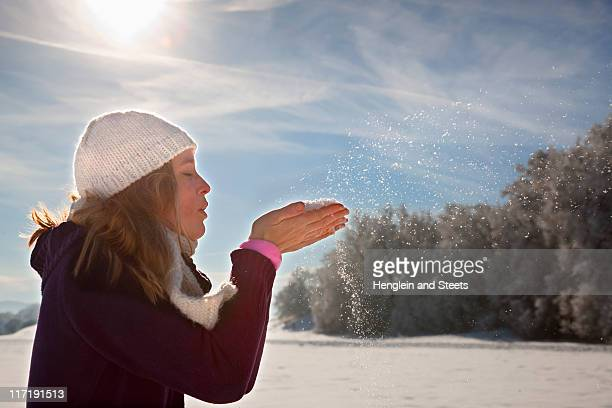 Woman blowing snow from hands