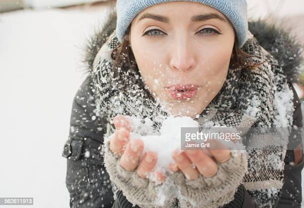 Woman blowing snow towards camera