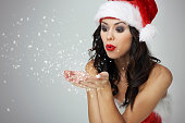 Woman blowing some small snow pieces