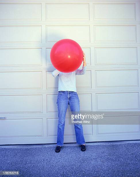 Woman blowing up balloon in front of garage door, USA