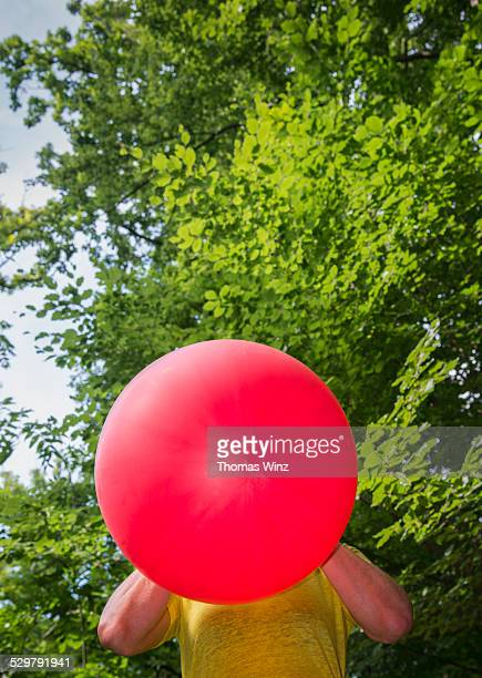 Woman blowing up red balloon