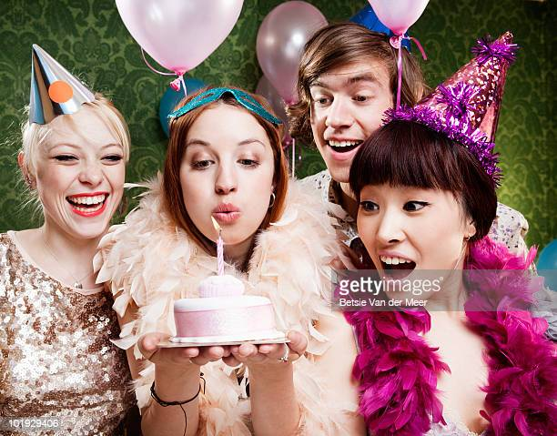 woman blows out candle on cake, with friends.