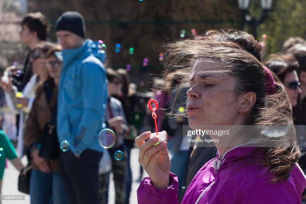 Woman blows soap bubbles during the Dreamflash soap bubble festival at the Pervomaisky Square in Novosibirsk, Russia, on April 30, 2016.