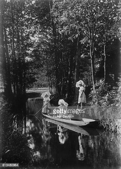 A woman boards a punt from a riverbank overhung with trees | Location Speewald Germany
