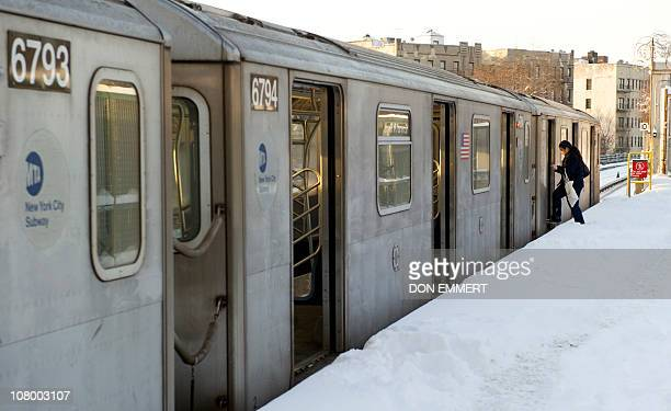 A woman boards a subway train from a snow covered platform at a Bronx stop January 12 2011 in New York The Northeast US was hit by its second major...