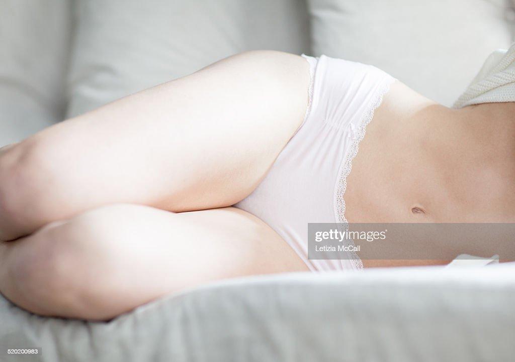 Woman body in underwear lying on a sofa