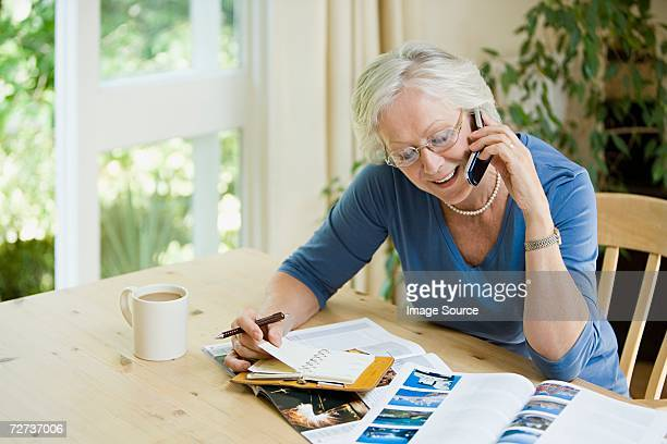Woman booking a holiday on cell phone