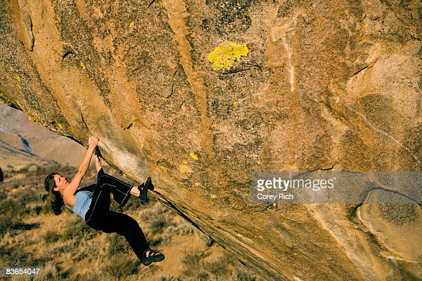 Woman bouldering on an overhang