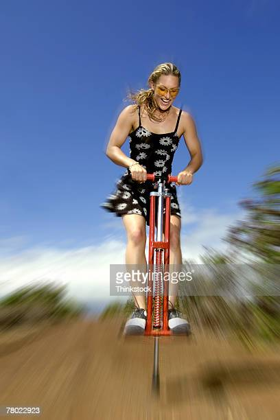 Woman bouncing on pogo stick